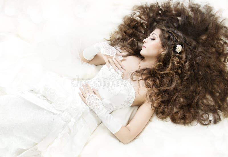 Sposa addormentata con capelli ricci lunghi che si trovano giù immagine stock libera da diritti