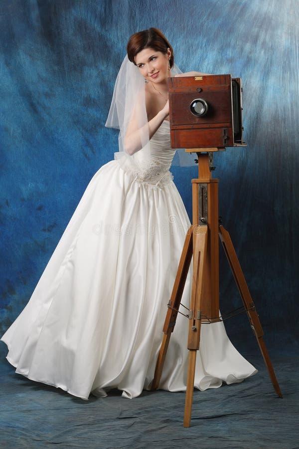 Sposa affascinante con una vecchia macchina fotografica fotografia stock libera da diritti