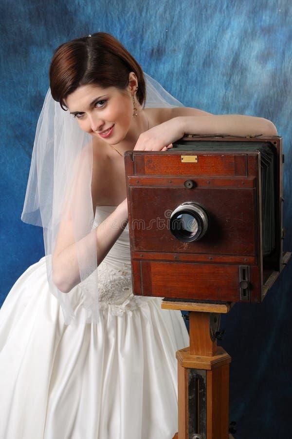 Sposa affascinante con una vecchia macchina fotografica fotografia stock