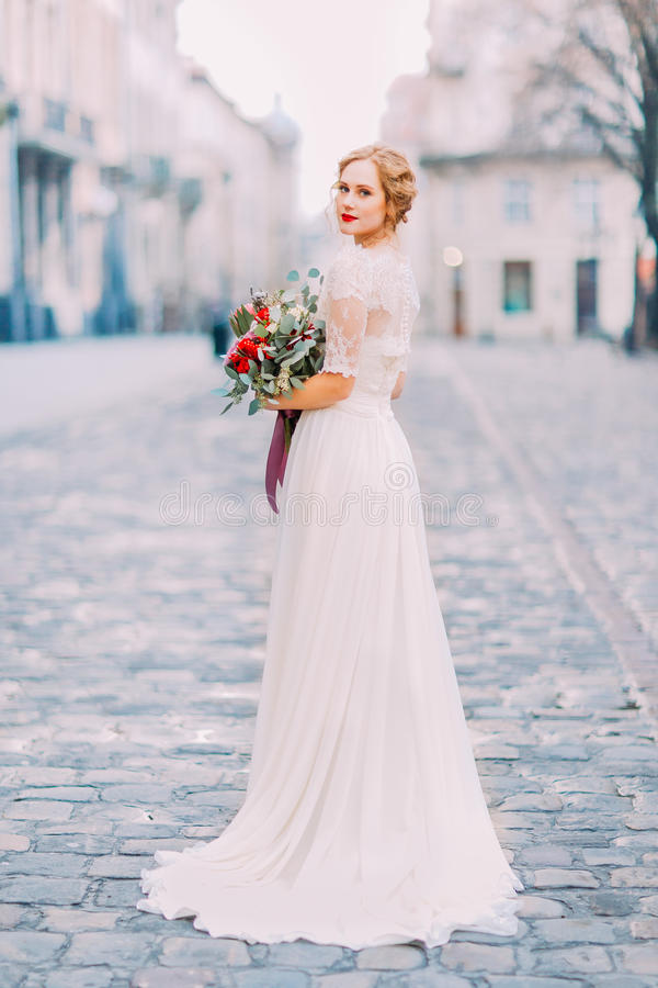 Sposa affascinante nel mazzo d'annata dal pizzo della tenuta lunga del vestito che esamina spalla nella macchina fotografica con  immagini stock libere da diritti