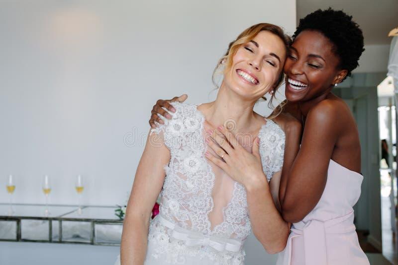 Sposa allegra e damigella d'onore sul giorno delle nozze fotografia stock libera da diritti