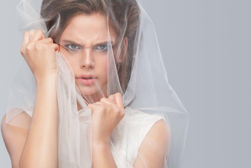 Sposa arrabbiata con l'acconciatura di nozze di modo - su fondo grigio Ritratto del primo piano di giovane sposa splendida nozze  fotografia stock libera da diritti