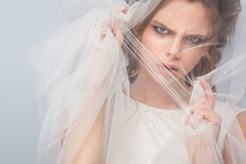 Sposa arrabbiata con l'acconciatura di nozze di modo - su fondo grigio Ritratto del primo piano di giovane sposa splendida nozze  immagini stock libere da diritti