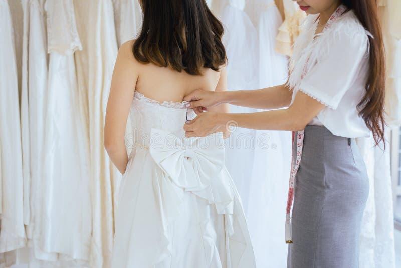 Sposa asiatica che prova sul vestito da sposa, adattarsi del progettista della donna del vestito che procede all'adeguamento nell fotografia stock