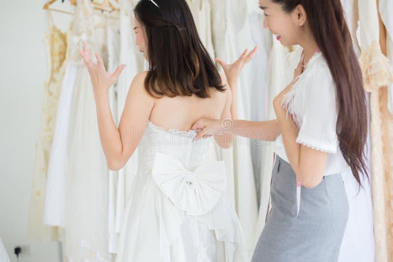 Sposa asiatica che prova sul vestito da sposa, progettista della donna che procede all'adeguamento nello studio di modo fotografia stock libera da diritti