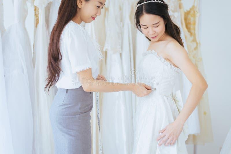 Sposa asiatica che prova sul vestito da sposa, progettista delle donne della donna che procede all'adeguamento lei fotografia stock