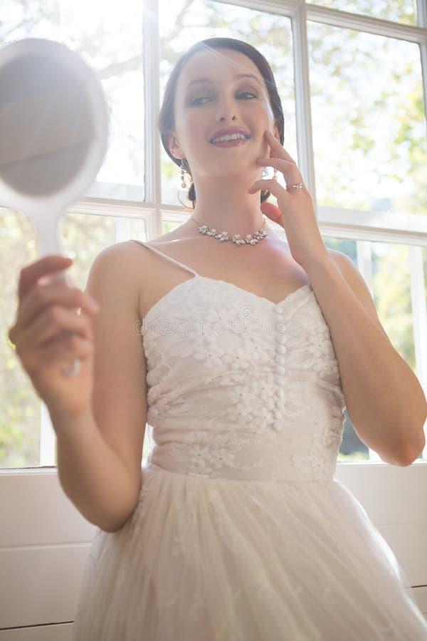 Sposa attraente che esamina specchietto mentre facendo una pausa finestra a casa immagine stock