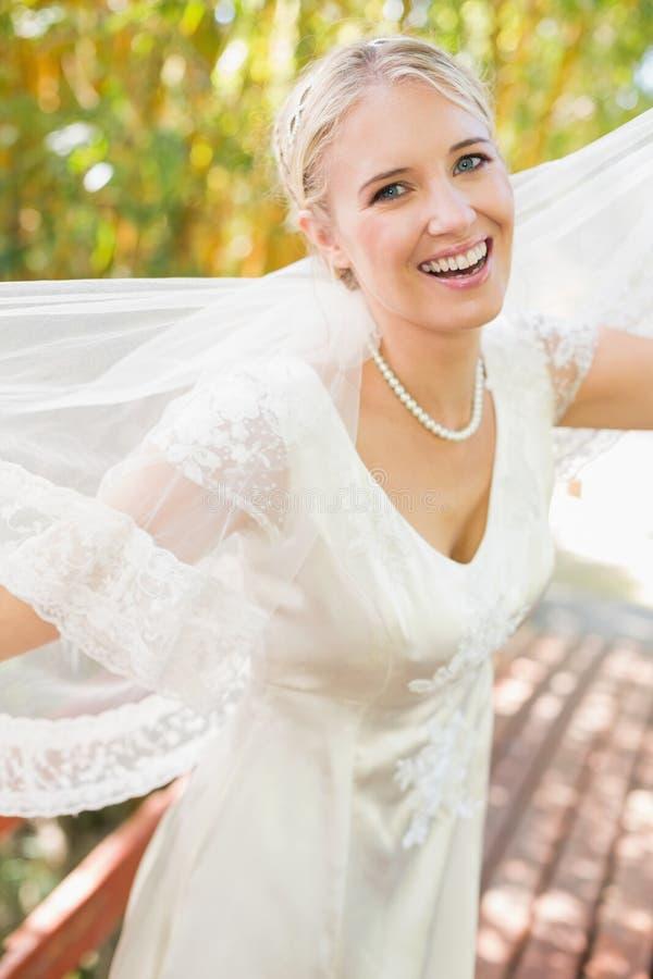 Sposa bionda abbastanza felice che tiene il suo velo fuori che sorride alla macchina fotografica fotografia stock