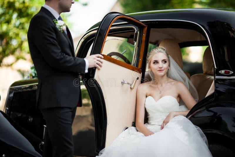 Sposa bionda alla moda splendida che posa in retro automobile nera con il gro fotografia stock libera da diritti