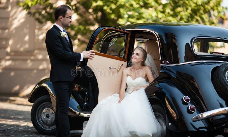 Sposa bionda alla moda splendida che posa in retro automobile nera con il gro immagine stock