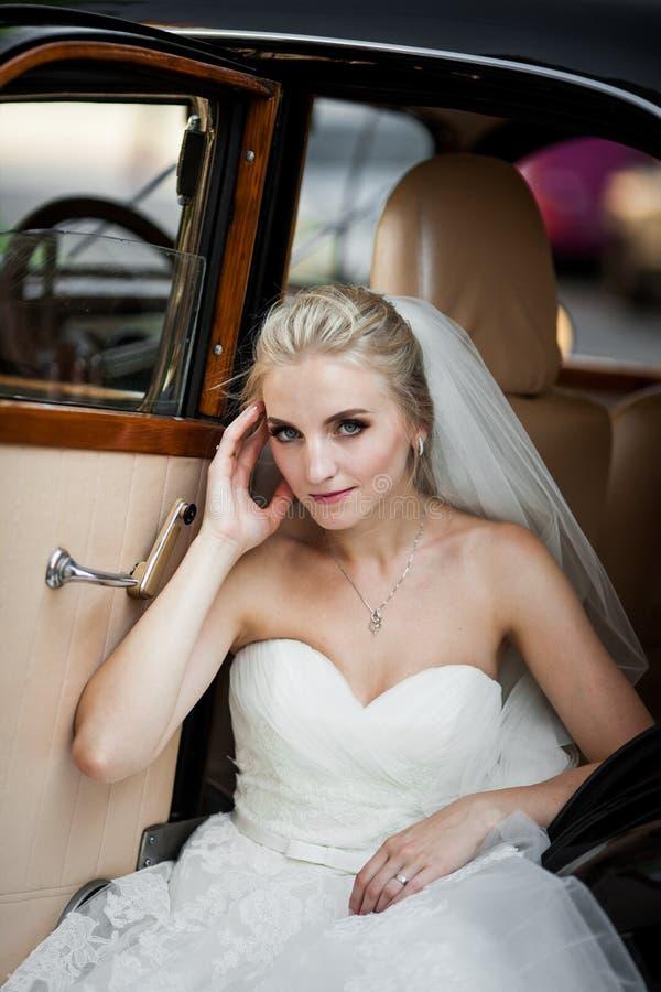 Sposa bionda alla moda splendida che posa in retro automobile nera nel bianco immagine stock