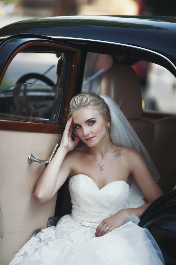 Sposa bionda alla moda splendida che posa in retro automobile nera nel bianco fotografie stock libere da diritti