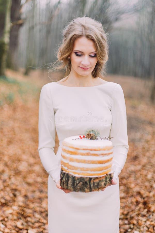 Sposa bionda attraente con la torta nunziale nella foresta di autunno fotografie stock