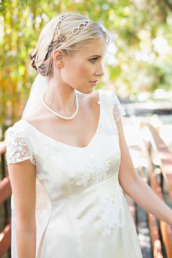 Sposa bionda calma in collana della perla che sta su un ponte fotografie stock