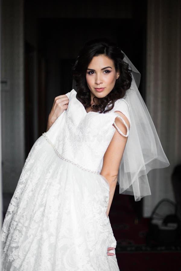 Sposa castana splendida che posa con il vestito da sposa bianco di lusso a fotografie stock