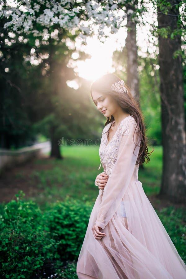 Sposa castana in vestito beige dal pizzo lungo di nozze, la decorazione della bella ragazza sessuale sui capelli all'aperto, in u immagine stock