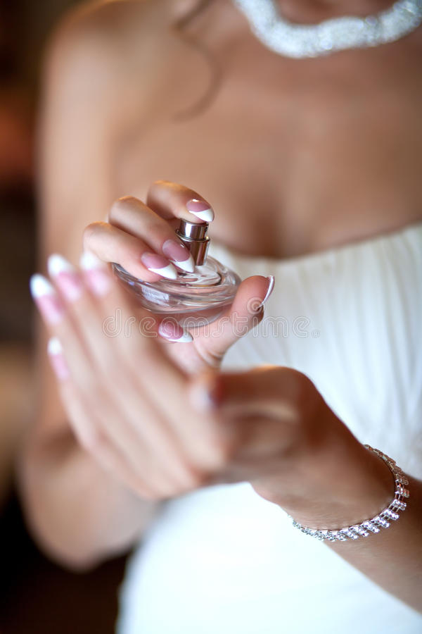Sposa che applica profumo sulla sua manopola immagini stock libere da diritti