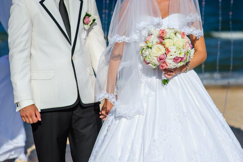Sposa che cammina con lo sposo nelle mani di bello bou di nozze fotografia stock libera da diritti