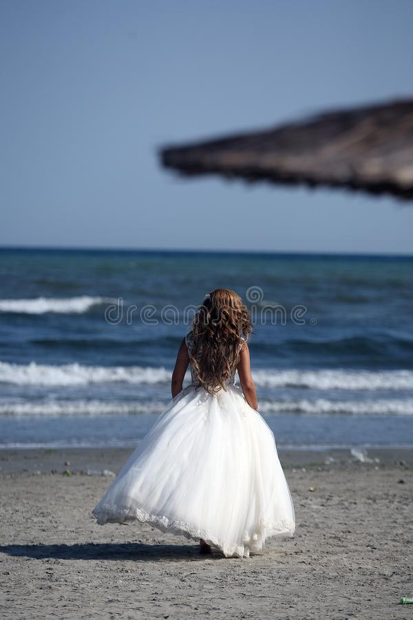 Sposa che cammina sulla spiaggia, lato posteriore immagine stock libera da diritti