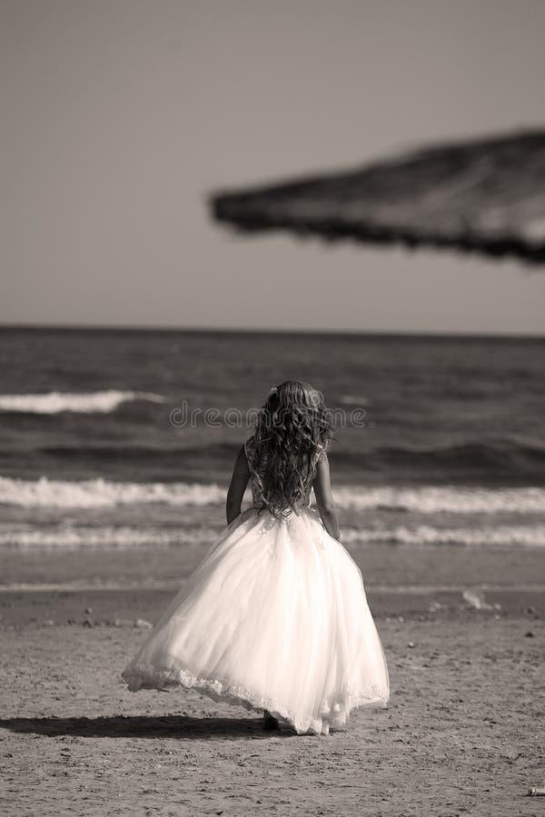 Sposa che cammina sulla spiaggia, lato posteriore immagini stock