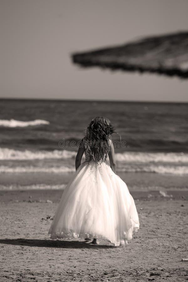 Sposa che cammina sulla spiaggia, lato posteriore fotografie stock libere da diritti