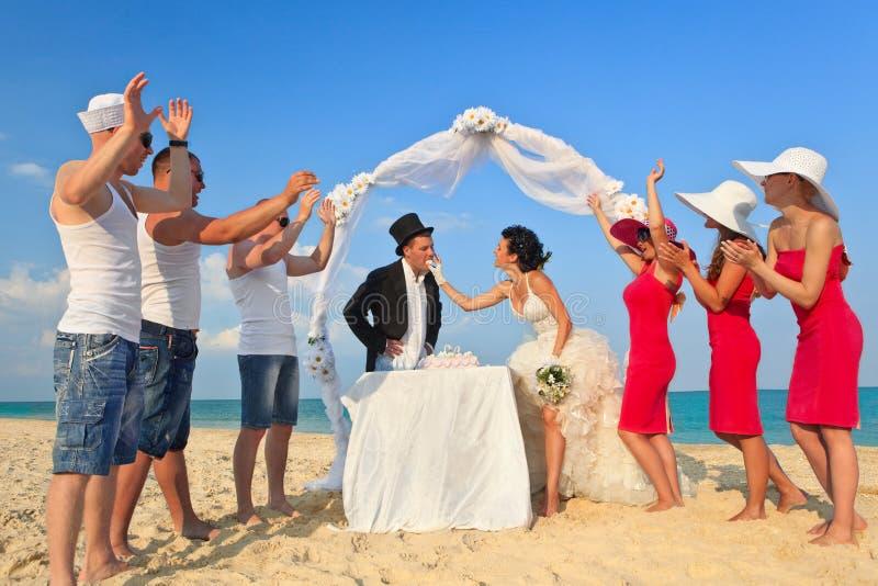 Sposa che dà al suo sposo un morso della torta di cerimonia nuziale. fotografia stock