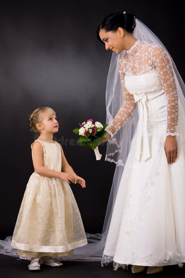 Sposa che dà fiore alla damigella d'onore fotografia stock libera da diritti