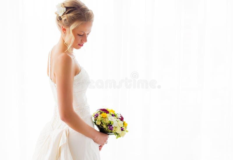 Sposa che fa una pausa la finestra nel suoi vestito da sposa e mazzo fotografie stock