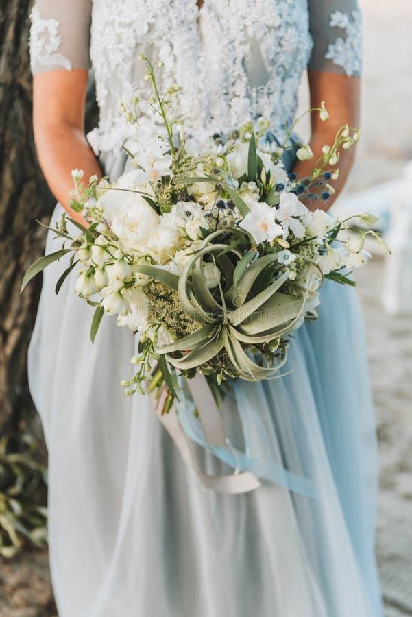 Sposa che indossa il mazzo blu-chiaro della tenuta del vestito da sposa fotografia stock