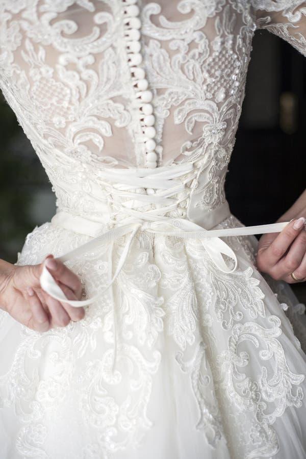 Sposa che mette sul suo vestito da sposa bianco fotografia stock libera da diritti