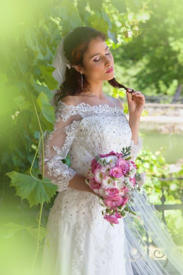 Sposa che posa nel fogliame verde fotografia stock libera da diritti