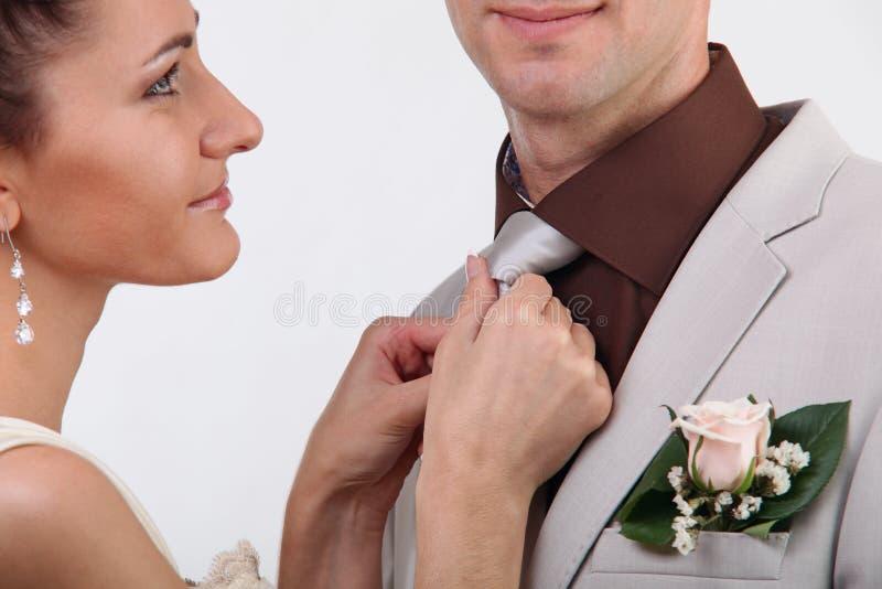 Sposa che registra il legame dello sposo fotografia stock