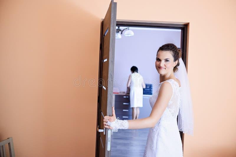 Sposa che sta alla porta nel salone fotografia stock