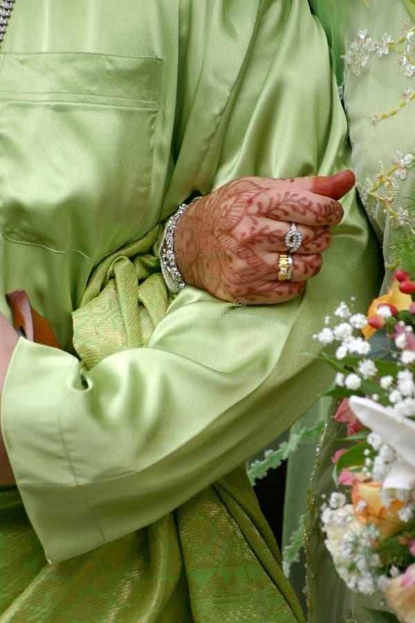 Sposa che tiene la mano stretta dello sposo fotografie stock