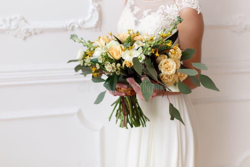 Sposa che tiene un mazzo dei fiori in uno stile rustico, mazzo di nozze immagine stock