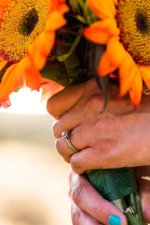 Sposa che tiene un mazzo dei girasoli variopinti fotografia stock libera da diritti