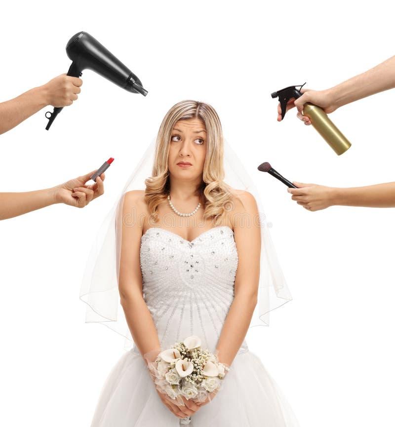 Sposa circondata a mano che tengono spazzola, l'essiccatore del colpo e rossetto immagini stock libere da diritti