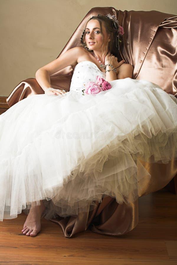 Sposa con capelli lunghi marroni che si siedono nella presidenza immagini stock libere da diritti