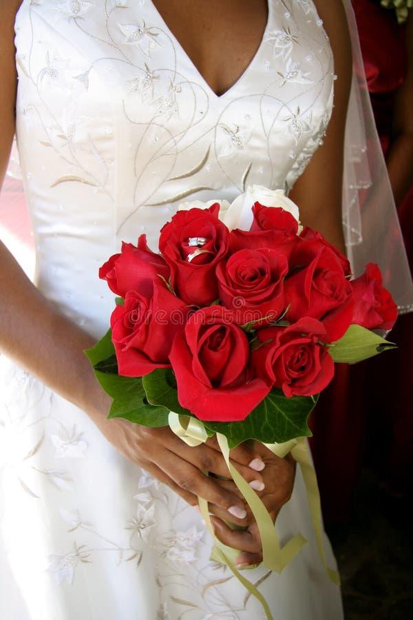 Sposa con gli anelli di cerimonia nuziale in mazzo rosso immagini stock libere da diritti