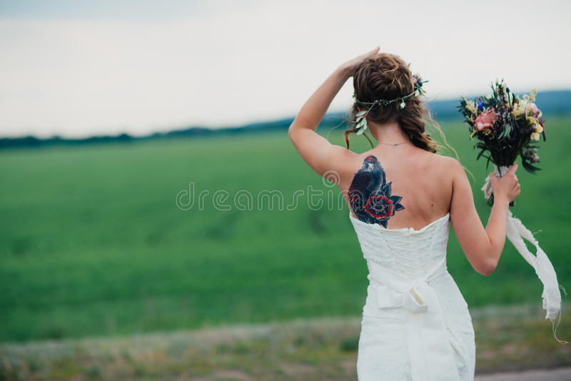 Sposa con i tatuaggi un mazzo sul campo verde immagini stock