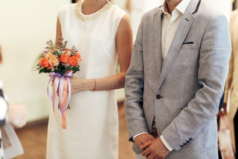 Sposa con il mazzo e sposo alla registrazione di nozze Coppie alla moda immagini stock