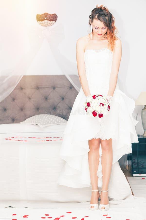 Sposa con il mazzo Letto di matrimonio della camera da letto fotografia stock