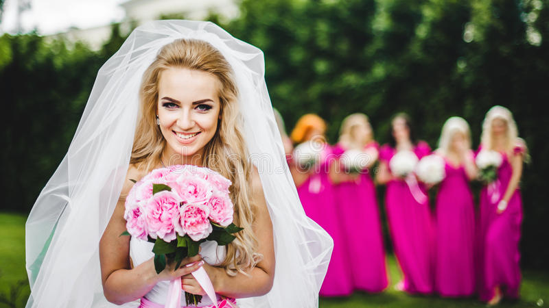 Sposa con le damigelle d'onore in un parco fotografie stock