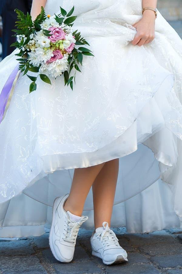 Sposa con un mazzo di nozze vestito in vestito bianco che mostra le scarpe da tennis sulle sue gambe immagine stock