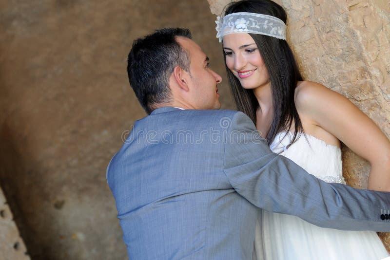 Sposa d'avvicinamento dello sposo in un magazzino fotografie stock libere da diritti