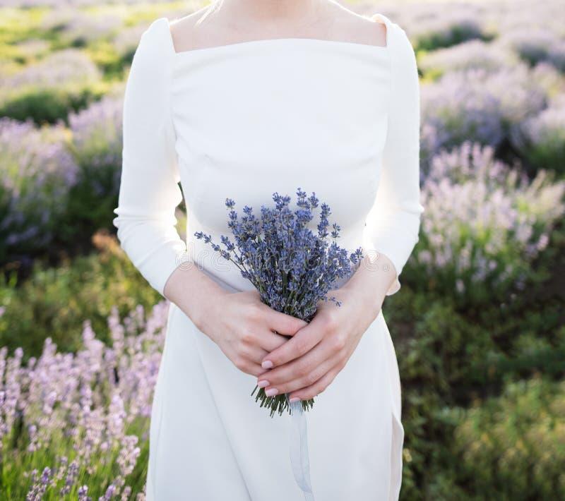Sposa della donna, tenente nel mazzo delle mani dei fiori della lavanda su fondo del campo, primo piano immagini stock libere da diritti