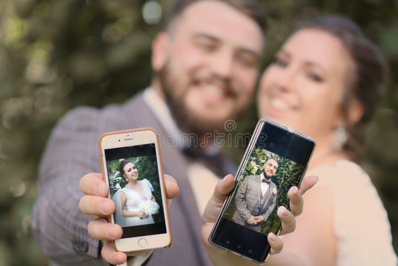 Sposa delle coppie di nozze con la fine del telefono di cellulari sulla foto fotografie stock libere da diritti