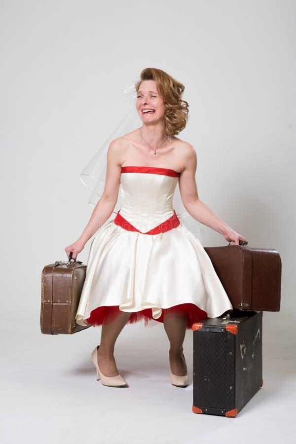 Sposa depressiva con le valigie su un fondo bianco nello studio fotografie stock