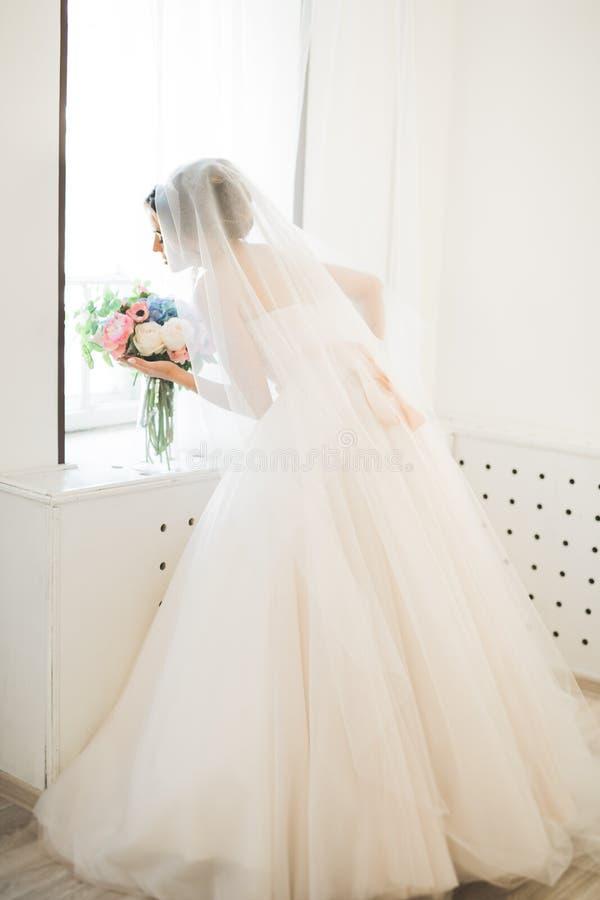 Sposa di lusso in vestito bianco che posa mentre preparando per la cerimonia di nozze fotografia stock