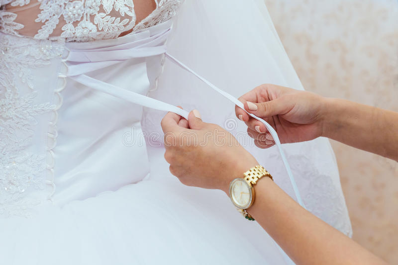 Sposa di mattina Damigella d'onore che aiuta allacciare il suo vestito immagine stock libera da diritti